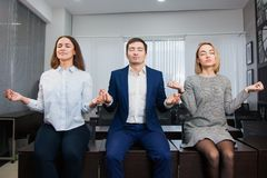 Three business poeple oor students meditate or procrastinate on office table. Stock Photography