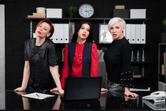 Three Business Women Stand Near Desk In Office Stock Photo