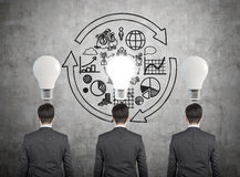 Three businessman. And drawing business concept with lamp stock photography