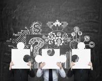 Three businessman holding puzzle Stock Photography