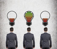 Three  businessman with lamp battery Royalty Free Stock Photo