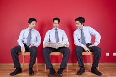 Three businessman reading a newspaper Royalty Free Stock Images