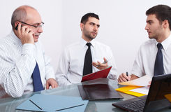 Three businessman sitting at table during meeting Stock Images