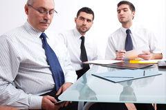 Three businessman sitting at table during meeting. Three businessman, one mature texting using his mobile phone and two young ones sitting at table during Stock Photo