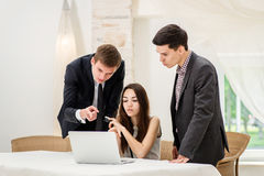 Three businessman sitting at the table and sit and watch work Royalty Free Stock Images