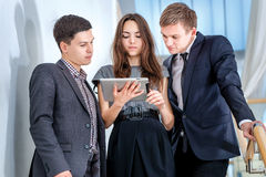 Three businessman standing on the stairs solve business problems. Several young people are at each other and smiling. People hold a tablet in the hands Stock Photo