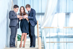 Three businessman standing on the stairs solve business problems. Several young people are at each other and smiling. People hold a tablet in the hands Royalty Free Stock Images