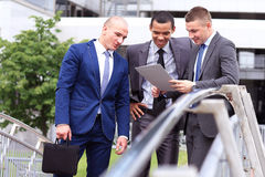 Three Businessmen Discussing Document Outside Office Royalty Free Stock Photos