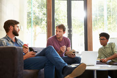 Three Businessmen Having Working Lunch In Office Stock Images