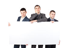 Three businessmen hold up a large blank sign Stock Photos