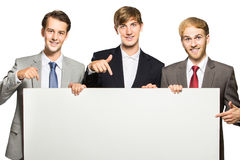 Three businessmen holding and pointing at white board Royalty Free Stock Photography