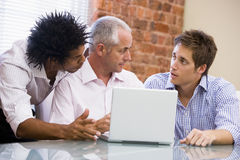 Three businessmen in office with laptop. Talking Stock Images