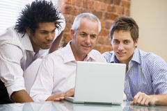 Three businessmen in office looking at laptop. Smiling Royalty Free Stock Image