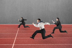 Three businessmen running on red track Royalty Free Stock Images