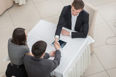 Three businessmen shaking hands at the table. Top view Stock Image