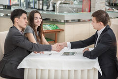 Three businessmen shaking hands at the table Royalty Free Stock Image