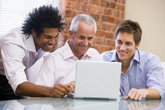 Three businessmen sitting in office with laptop Royalty Free Stock Images