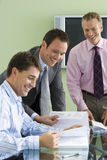 Three businessmen sitting and standing at desk in office, looking at documents, laughing stock photos
