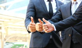 Three businessmen in team work thumbs up when they choose the best plan stock image