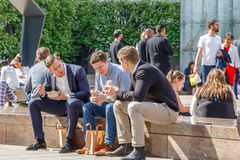 Three businessmen on their lunch break in Cabot Square, Canary Wharf Stock Photos