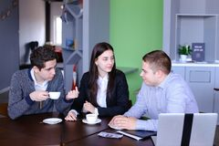 Three businessmen, woman and men discussing robot with cup of te royalty free stock photography