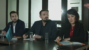 Three businessmens sits at the table and listens report. stock video footage