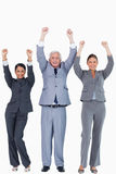 Three businesspeople with arms up Stock Photos