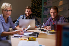 Three Businesspeople Having Late Meeting In Office Royalty Free Stock Photography