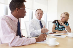 Three Businesspeople Having Meeting In Boardroom Stock Photography