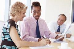 Three Businesspeople Having Meeting In Boardroom Stock Photo