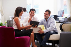 Three Businesspeople Having Meeting In Hotel Lobby Royalty Free Stock Images