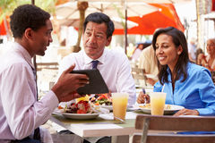 Three Businesspeople Having Meeting In Outdoor Restaurant Stock Image