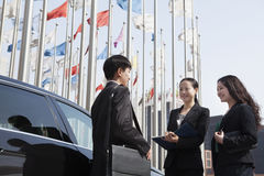 Three businesspeople meeting outdoors with flagpoles in background. Stock Image