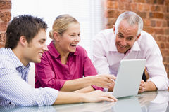 Three businesspeople in office with laptop stock image