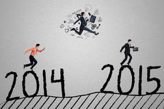 Three businesspeople in race to reach number 2015. Entrepreneurs running through number 2014 to 2015 and compete to achieve number 2015, symbolizing business Stock Photo