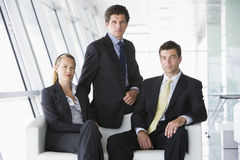 Three businesspeople sitting in office lobby. Looking at camera royalty free stock photo
