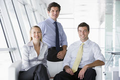 Three businesspeople sitting in office lobby. Smiling royalty free stock image