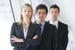 Three businesspeople standing in corridor Stock Images