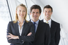 Three businesspeople standing in corridor smiling Stock Photos