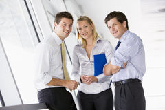 Three businesspeople standing in corridor smiling Royalty Free Stock Photos