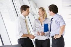 Three businesspeople standing in corridor talking Stock Photos