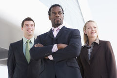Three businesspeople standing outdoors by building Royalty Free Stock Images