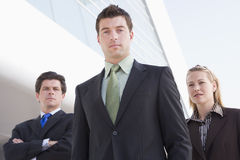 Three businesspeople standing outdoors by building Royalty Free Stock Image