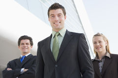 Three businesspeople standing outdoors by building. Smiling stock photography