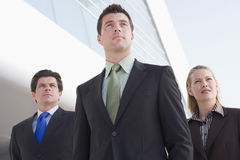 Three businesspeople standing outdoors by building Stock Photos