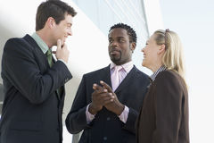 Three businesspeople standing outdoors by building. Talking and smiling royalty free stock photo