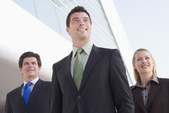 Three businesspeople standing outdoors by building. Smiling stock image