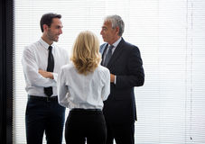Three businesspeople standing up and speaking Royalty Free Stock Photography