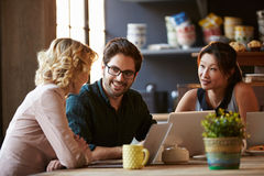 Three Businesspeople Working At Laptop In cafe Royalty Free Stock Photos
