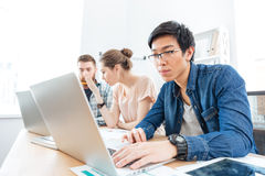 Three businesspeople working in office with laptops Stock Photos